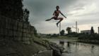 Odvážný romský chlapec skáče do řeky